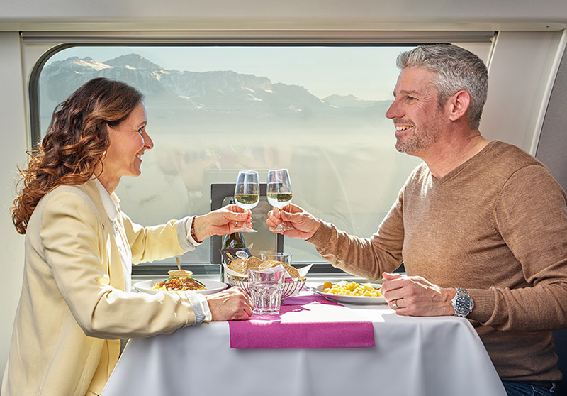 Woman and a men sitting at a table in the dining car and cheering with champagne